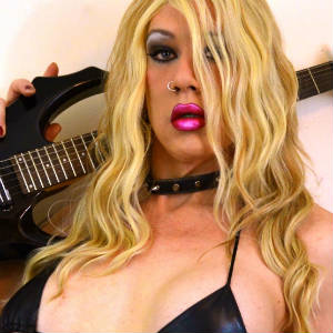 Photo of Kimber Haven in black leather bikini top with a guitar on her shoulder.