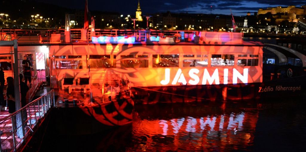 """A picture of a boat with red lights blasting it and a large """"Jasmin"""" projected over it all."""