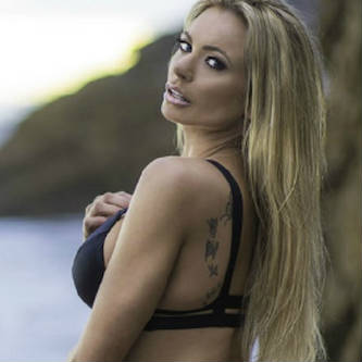 Beach-set photo of Briana Banks looking back over her shoulder in a black bikini.