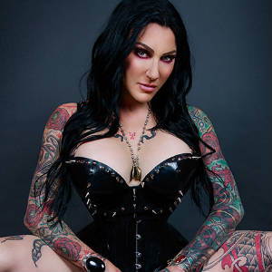 Portrait of Jenevieve Hexxx in a wasp-waisted latex corset showing off the tattoos on her arms and thighs.