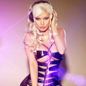 Promo photo of Andrews wearing headphones and a sexy cross-ribboned and revealing rubber dress.