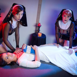 Promo Photo of Penny Pax, Adriana Chechik and Kayla Paris, as two sexorcist nuns and their possessed victim, lying on a bed before them.