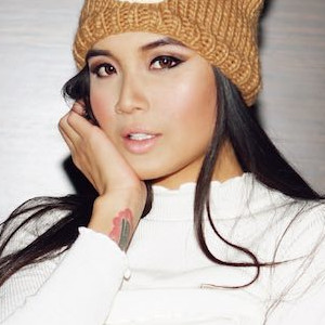 A close-up of Brenna Sparks looking insanely hot in a tuque and white cable-knit sweater.