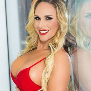 Promotional Close Shot of Busty Tegan James in a Provocative Red Dress
