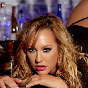 Close up glam shot of Brett Rossi on a bar holding a fancy drink.