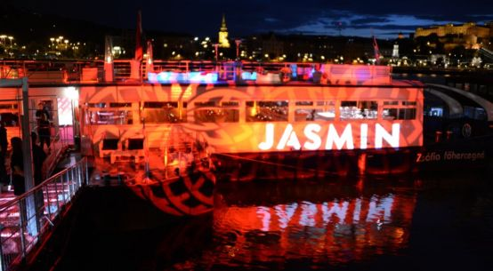 A picture of a boat with red lights blasting it and a large