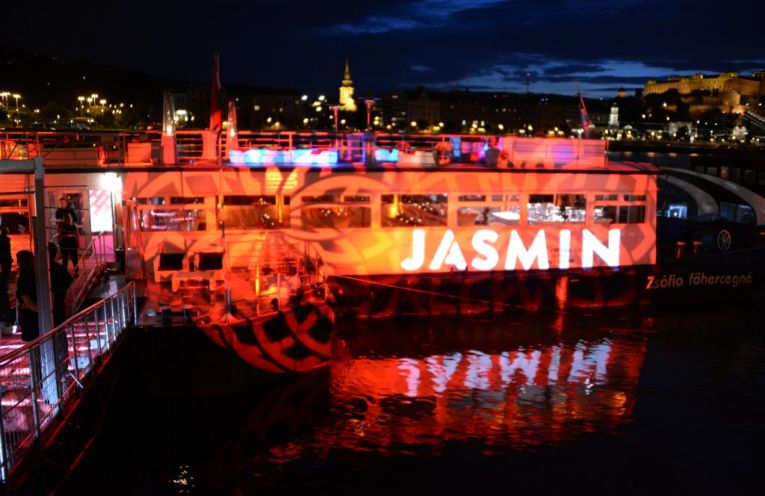 "A picture of a boat with red lights blasting it and a large ""Jasmin"" projected over it all."