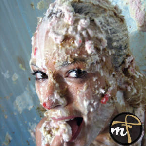 A photo of a woman smeared and covered with pie, cream, cake, and whatever....