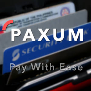 Out of focus photo of credit cards with the Paxum logo and motto superimposed.