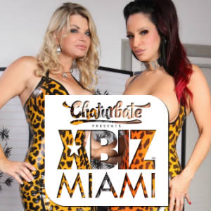 Photo of busty babes Vicky Vette and Rubberdoll in rubber dresses and the XBIZ Miami Logo.