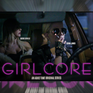A still from Girlcore, with Cherrie DeVille in the back seat of a car driven by Kenna James, who's also wearing dark glasses and smoking a cigarette.