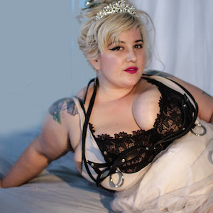 Photo of heavy, curvy Genevieve LaFleur reclining on a bed in a lace bra.