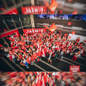 A high, wide photo of Jasmin Academy students raising arms to the camera - lotsa red!