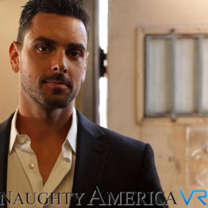A medium shot of Ryan Driller, his collar open, tieless, and the Naughty America VR logo.