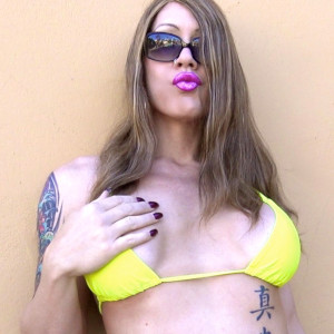 A photo of Kimber Haven in a yellow bikini top leaning agains a clam-coloured wall, wearing shades and looking snotty.