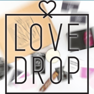The LoveDrop logo is superimposed over a zoom-blurry background of the contents of a subscription box.