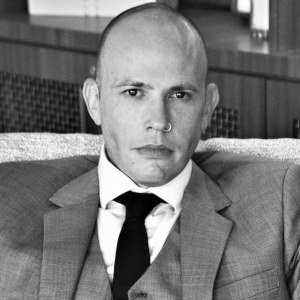 A black & white head shot of Alex Saint, looking bald and serious, in a suit and tie.