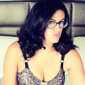 A medium shot of Penny Barber wearing glasses and a sexy black and striped bra.