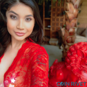 Fetching selfie of Brenna Sparks in a red and revealing Asian blouse, with the CoinRivet logo perhaps erroneously watermarked in the lower right corner... oh well.