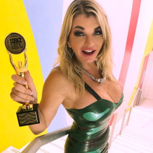 A photo of Vicky Vette holding her XBiz Award up to the higher-angled camera, providing a delicious view of her tight, shiny green dress.