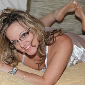 A photo of Lonestar Angel wearing glasses and lingerie, lying in a bed with her feet up behind her.