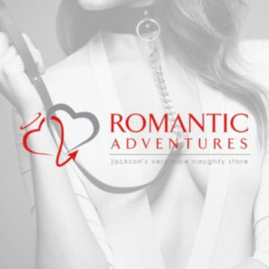 The Romantic Adventures logo over a low contrast black & white image of a woman with a low-cut blouse holding her own leash.