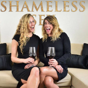 A photo of Amy and April in black dresses, sitting on a couch holding red wine glasses.