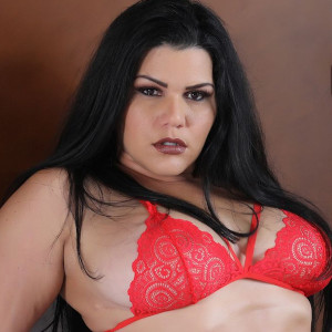 Medium closeup of voluptuous brunette in a red brassiere.