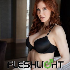 A promo photo of the fetching redhead in a black brassiere, holding a Fleshlight, with the company logo at the bottom.