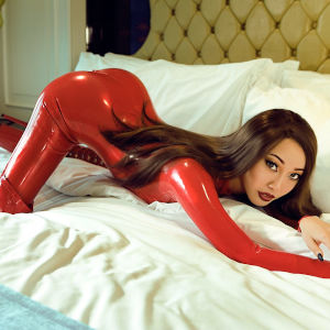 A photo of Mistress Eva in a tight red latex body suit, face down ass up in a big comfy bed.
