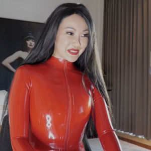 A medium shot of Mistress Eva in tight red latex smiling at something out of frame, probably on her laptop.