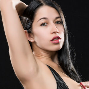 A studio photo of Alex Coal posing in a black leather bikini top.