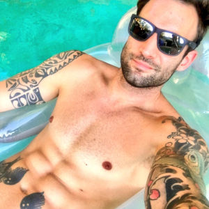 A slick-looking selfie by Alex Legend of him wearing shades, floating comfortably in an inflatable pool chair.