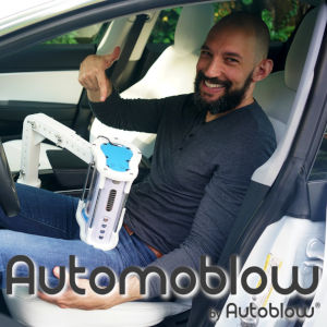 A photo of the Automoblow inventor sitting in his car with the device attached.