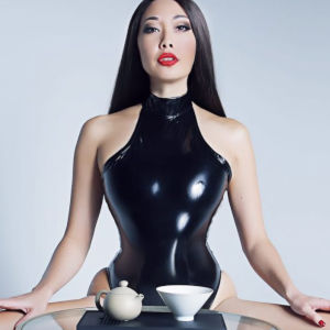 A symmetrical portrait of Mistress Eva in latex before a small tea-service table.